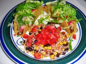 Taco's w/Spicy Hamburger Meat, A Little Cheese/Sour Cream, Tomato & Lettuce and a Side of Rice w/Black Beans, Corn, Salsa & Tomatoes on Top!