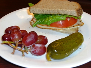 Boar's Head oven-gold turkey/cheese/tomato/lettuce sandwich, grapes & a pickle